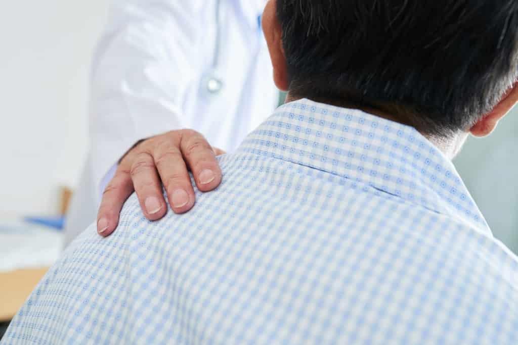 A chiropractor talks to a sciatica sufferer