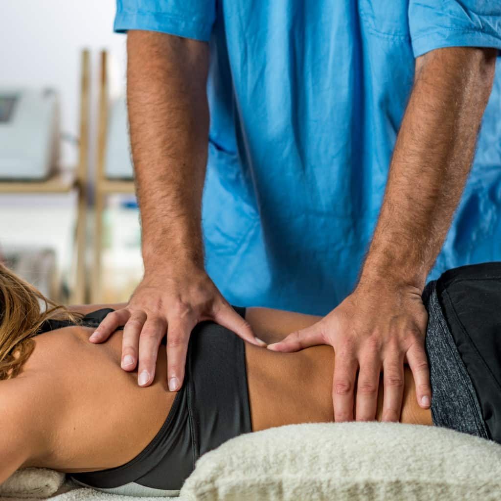 A chiropractor works on a patient