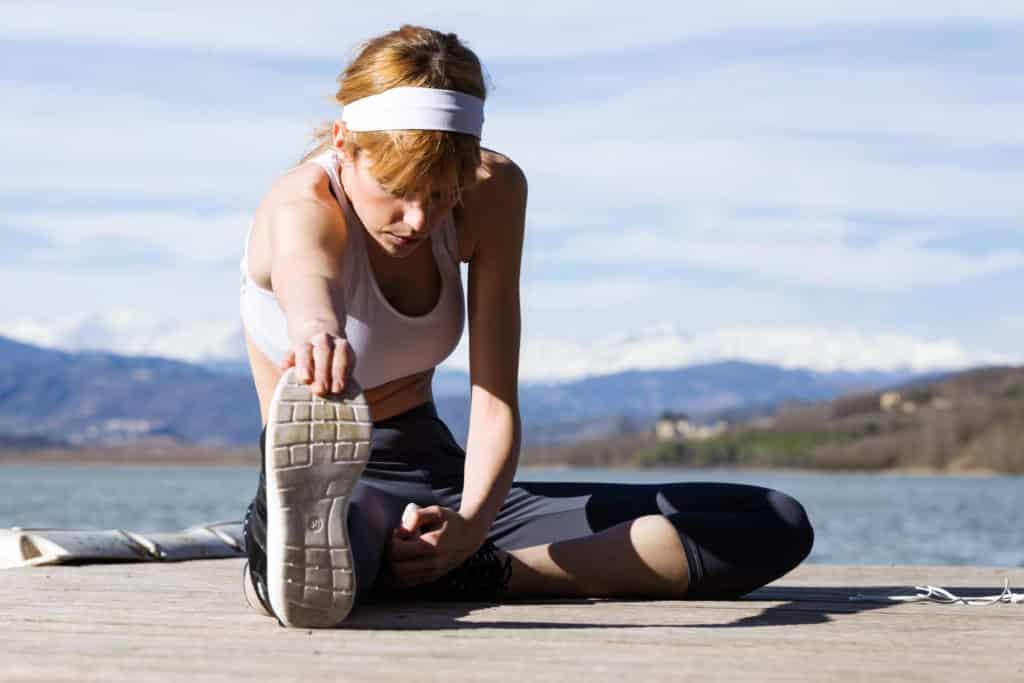 Woman stretching lumbar spine at the lake