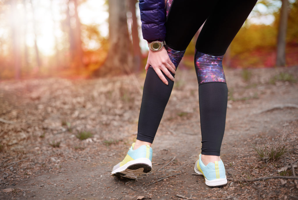 A woman pauses during her run due to knee pain.