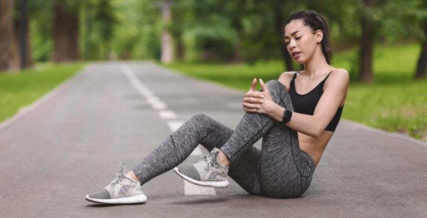 A young woman takes a break from running due to a knee problem