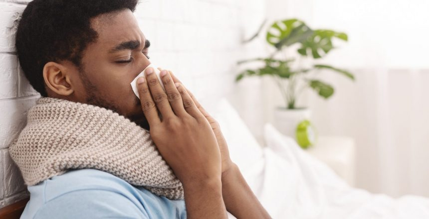 Young sick man in bed cleaning snotty nose